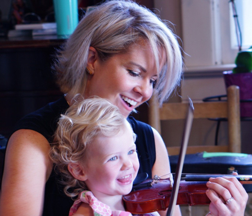 Teacher teaching child violin
